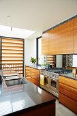 Elegant kitchenette with walnut fronts and kitchen island