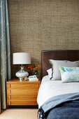Double bed with leather headboard, bedside table with lamp and textile wallpaper in the bedroom