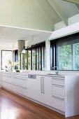 White kitchenette under windows in bright kitchen