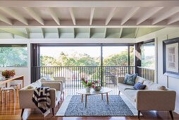 Bright upholstered furniture and coffee table in an open living area with a window front