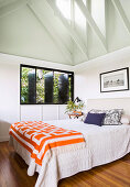 Double bed in a bright bedroom with a gable roof