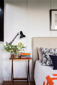 Bedside table with lamp, branch of leaves and books next to bed with headboard