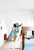 Bunk bed in white children's room, boy on bed ladder