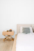 Double bed with headboard and bedside table in white bedroom