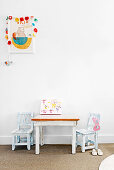 Children's table with two chairs in front of white wall, above with picture with garland