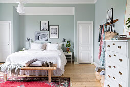 Bed in niche with pictures on wall in pale blue bedroom