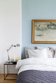 Wintry landscape painting on blue wall above bed