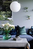 Vase of flowers on coffee table with concrete top below spherical lamp and in front of sofa with scatter cushions in living room with grey wall