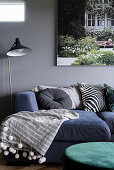 Blue sofa combination with scatter cushions and blanket, standard lamp and picture on grey living-room wall