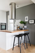 Hob and wooden worksurface on white counter, bar stools, extractor hood and marble tiles on grey wall