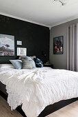 Double bed in bedroom with dark walls