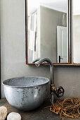 Vintage tap fitting and metal basin below mirrored cabinet in bathroom