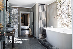 Vintage washstand with metal basins opposite free-standing bathtub below window decorated with branches
