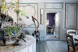 Vases and flower arrangements on podium in room with painted panelled walls