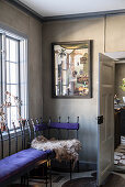 Metal bench with purple cushions in corner of room with artwork on grey-brown wall