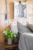 Picture of elephant on wooden wall above bed and vase of lilac on bedside table
