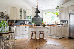 Large open-plan country-house kitchen in natural shades