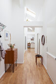 Retro chest of drawers and stool in white hallway with skylights