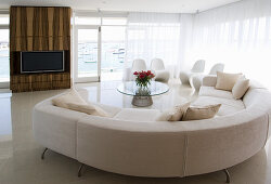 White designer sofa in front of window and wood-clad TV cabinet in open-plan interior