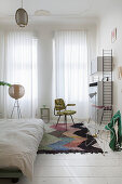 White bedroom in period building decorated with retro furniture