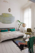 Retro furniture and splashes of colour in white bedroom in period building