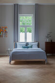 Double bed in front of window in bright, spacious bedroom