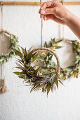 Hand-tied wreaths of dried leaves, flowers and grasses