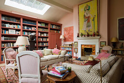 Library, antique armchairs and sofa in front of fireplace in living room in shades of pink