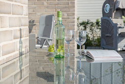 Glass table on terrace of house clad in pale brick