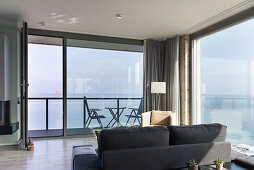 Interior with floor-to-ceiling glass walls looking onto terrace and to sea view