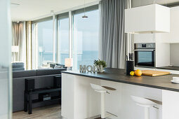 Floor-to-ceiling glass walls with sea view and open-plan kitchen with island counter and barstools