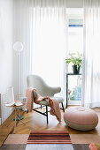 Armchair with round pouffe and pink accessories next to window