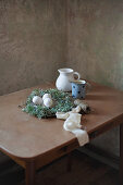 Speckled eggs in Easter nest and jugs on table