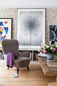 Grauer Sessel vor dem Bild einer Pusteblume im Wohnzimmer