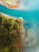 Bird's-eye view of woodland on shore of cobalt-blue water