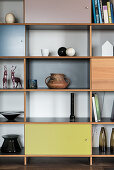 Minimalist decoration on shelving with compartment doors in various colours