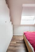 Cupboards below sloping ceiling in attic bedroom
