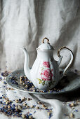 Vintage coffee pot with floral motif on pewter plate