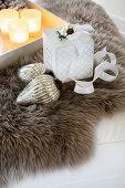 Christmas-tree bauble, gift box and tray of tealights on fur rug