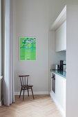 Stuhl vor schlichter Einbauküche in Altbauwohnung, Plakat an der Wand