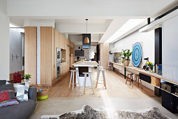 Fitted kitchen with wooden fronts and island, continuous wooden plate as a desk in an open living room