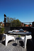 Woman relaxes on roof terrace with designer furniture