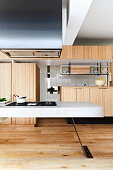 Fitted kitchen with wooden fronts and white island in an open living room
