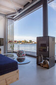 Modern houseboat: log burner in front of glass wall
