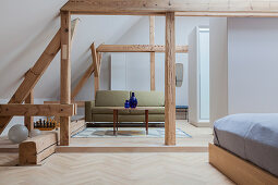 View from sleeping area to sofa in living area of open-plan interior