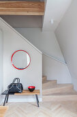Bag and bowl on bench below round mirror in stairwell