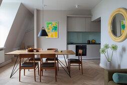 Schlichte Einbauküche und Essbereich in offenem Wohnraum