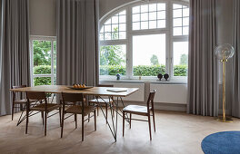 Dining table with wooden top and chairs in front of arched window in period apartment