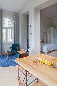 Blick über Esstisch auf Sitzecke und Schlafbereich in offenem Wohnraum