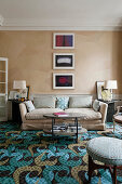 Beige silk wallpaper, sofa and patterned carpet in living room